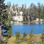 can't really see them, but 2 girls together in weird pose on tiny islet in a Cathedral Lake
